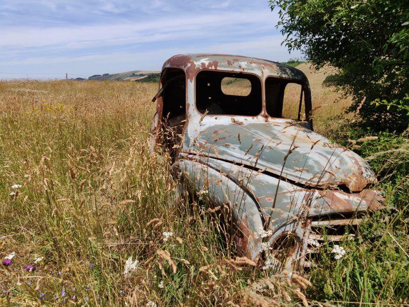 Auf einer Wiese mitten in der Landschaft rostet ein alter Citroën vor sich hin.